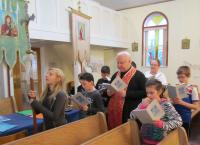 "Children doing Stations of the Cross with Fr. Emil and catechism teacher Pat Gawaziuk. In the background are imitation ""stained glass"" crosses, which the children made to decorate church windows."