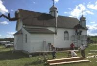 Volunteers putting on vinyl siding on 95 year old Holy Eucharist Church in Horod, Manitoba (23 km NW of Sandy Lake, MB).
